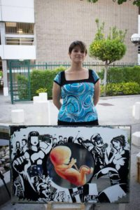 Licet Romero stands behind her painting she created for the Visions of Words poetry event.