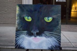 Greg Stanley created a poem and painting inspired by the green color of his cat's eyes. He read the poem and showed the painting at the Visions of Words event.